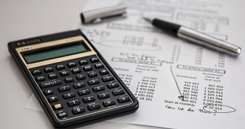 Stock photo of a calculator on top of a monthly expenditure report