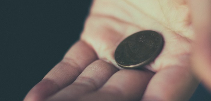 Stock photo of a white hand holding a single coin