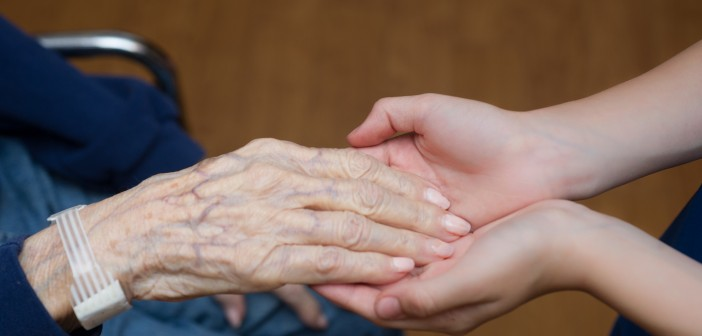 Stock photo of an older person's hand in the hands of a younger person