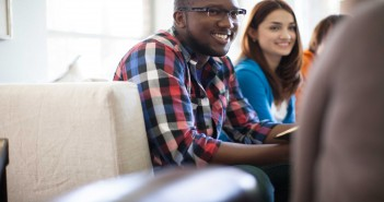 Stock photo of a young African American man and a young white woman in a fellowship group