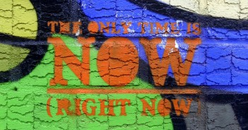 "Stock photo of graffiti on a concrete wall that reads ""the only time is NOW (right now)"
