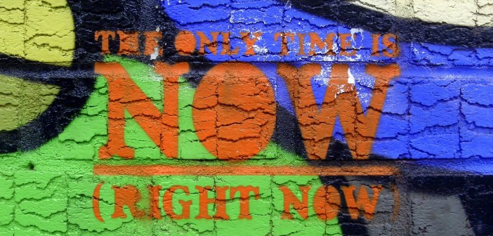 """Stock photo of graffiti on a concrete wall that reads """"the only time is NOW (right now)"""