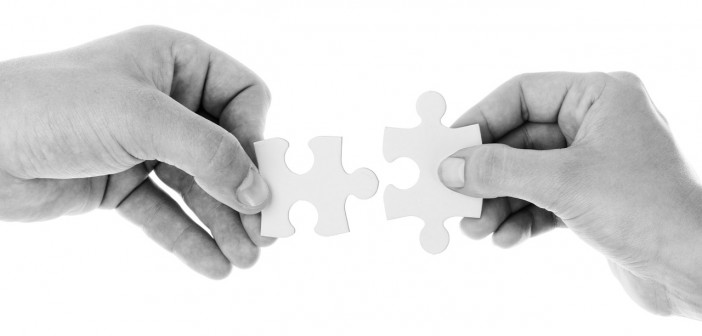Black and white stock photo of two individuals putting two puzzle pieces together