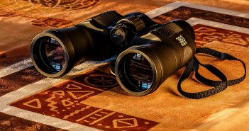 Stock photo of a pair of binoculars on a throw rug