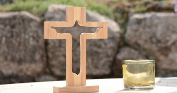 Stock photo of an outdoor altar with a small, wooden cross with a silhouette of Jesus cut out of it and a lit votive candle to its right