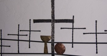 Stock photo of six black, hammered metal crosses with a gold hammered chalice and a copper hammered communion plate