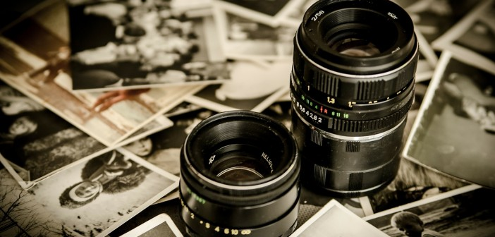Stock photo of two DSLR camera lenses among a pile of black-and-white photos