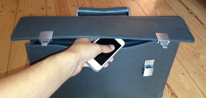 Stock photo of an individual putting an iPhone in a briefcase