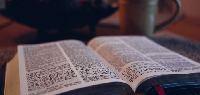 Stock photo of an open bible on a table with a coffee mug in the background