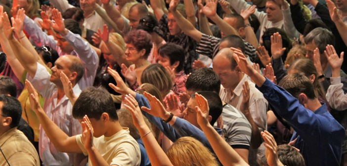 Stock photo of a large group of white people extending their arms upward during worship