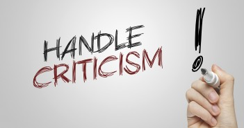 "Stock photo of a hand writing ""HANDLE CRITICISM!"" on a whiteboard"