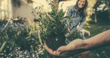Stock photo of a gardener unearthing a flower with a smiling woman in the background