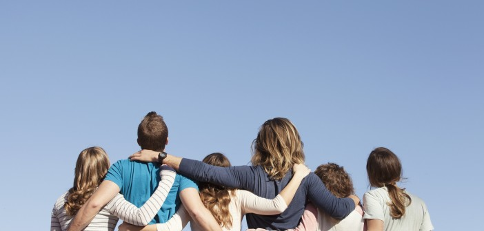 Stock photo of the backs of a white family - mom, dad, and four daughters - looking up at the sky