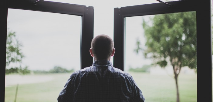 Stock photo of a white man facing an open window