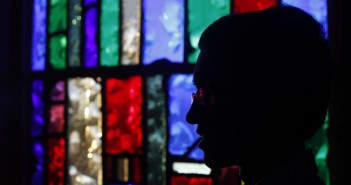 Stock photo of a silhouette of an individual sitting in a room back-lit by stained glass windows