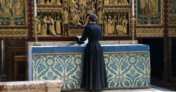 Stock photo of a clergywoman at an altar preparing for services