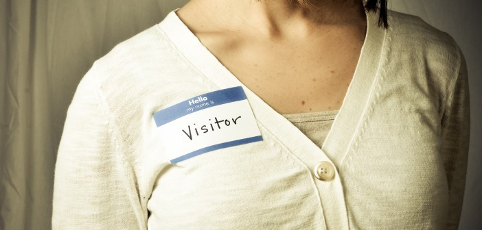 "Stock photo of a white woman wearing a nametag that reads ""hello my name is VISITOR"""
