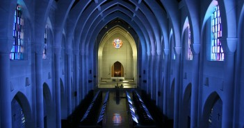 Stock photo of the interior of an empty sanctuary with the lights turned off and sunlight pouring in through the stained-glass windows
