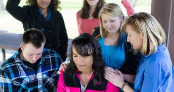 Stock photo of a group of young individuals of mixed genders and races praying over one of their peers