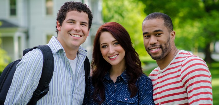 Stock photo of three young individuals - a white man, a white woman, and an African American man - posing for a portrait outside of a house