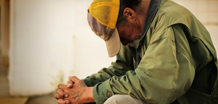 Stock photo of a grungy, tattooed white man who is praying