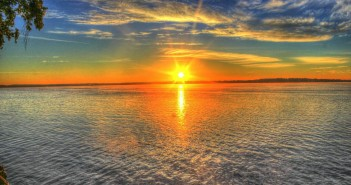 Stock photo of the sun rising or setting over a lake