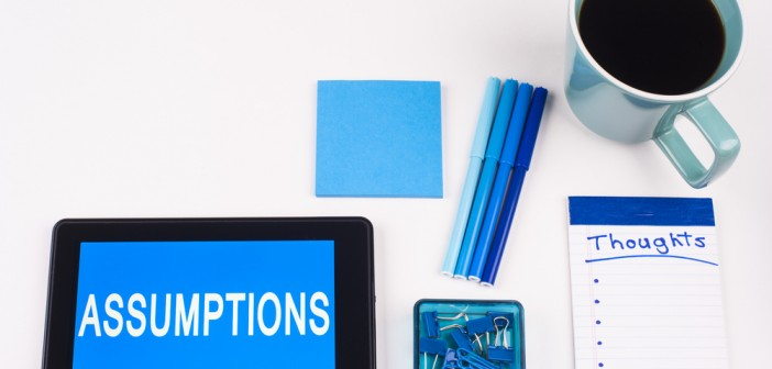 """Stock photo of a tablet that has the word """"ASSUMPTIONS"""" on it, a stack of blue post it notes, a group of blue pens, a notepad that has """"THOUGHTS"""" written on it and a cup of coffee"""