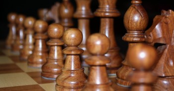 Closeup stock photo of a set of black chess pieces carved out of wood
