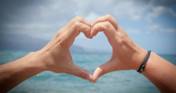 Stock photo of a pair of hands forming a heart looking out over a body of water