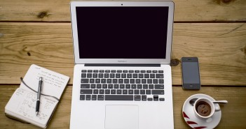 Stock photo of someone's workspace that has a moleskine notebook, a MacBook Air, an iPhone, and a cup of espresso