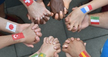 Stock photo of a diverse group of interlocked hands with different flags painted on their wrists