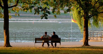 Stock photo of two people on a bench in a park by a waterfront in Germany