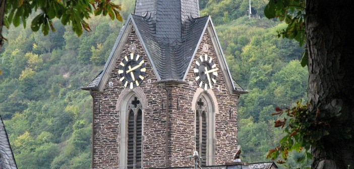 Stock photo of a steeple/bell tower with a clock on it in the mountains. It is approximately 4:10 in the afternoon.