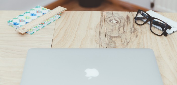 Stock photo of an Apple laptop on a wooden table