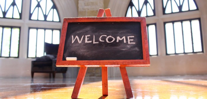 "Stock photo of a small chalkboard in the middle of a room that has ""WELCOME"" written on it"