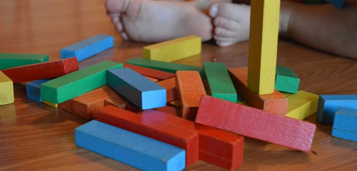 Stock photo of a baby playing with multi-colored blocks