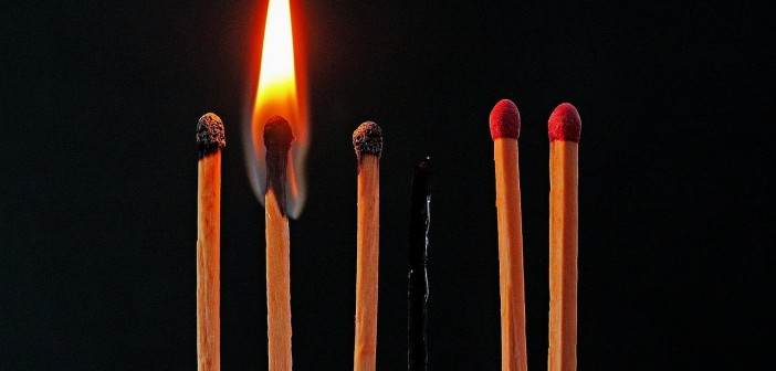 Stock photo of seven matches: two that have not been lit ever, one that is currently lit, two that have been lit but are now extinguished, and one that is completely burnt out