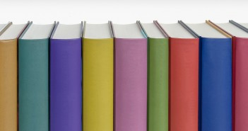 Stock photo of a bunch of standing books pressed against one another - as if on a bookshelf - with a rainbow of colored spines with no titles