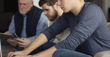 Stock photo of a mixed-age group of white men working on various electronic devices