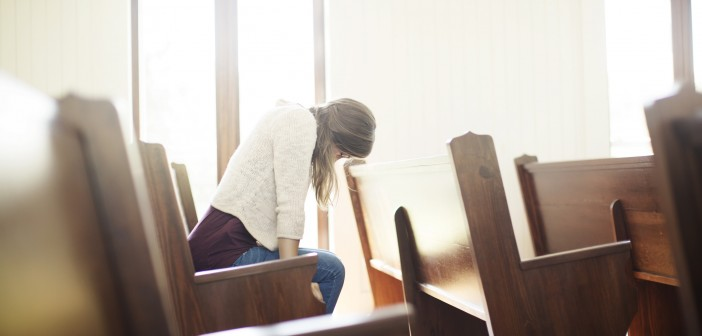 Stock photo of a young white woman praying by herself in a pew