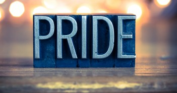 "Stock photo of the word ""PRIDE"" carved out of wood and painted silver"