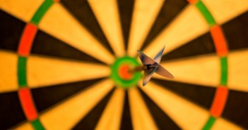 Stock photo of an empty, out-of-focus dartboard save for one, lone, in-focus dart on the bulls-eye