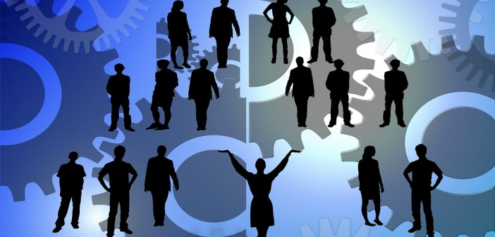 Clip art of a group of silhouettes of people in amidst a sea of gears