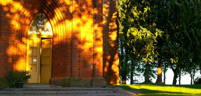 Stock photo of the exterior of a big brick church/chapel in a park.