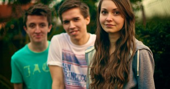 Stock photo of three white youth - two boys and one girl- outside