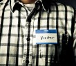 "Photo of an individual wearing a black-and-white checkered shirt and a nametag that reads ""hello my name is VISITOR"""