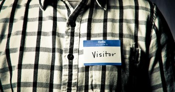 """Photo of an individual wearing a black-and-white checkered shirt and a nametag that reads """"hello my name is VISITOR"""""""