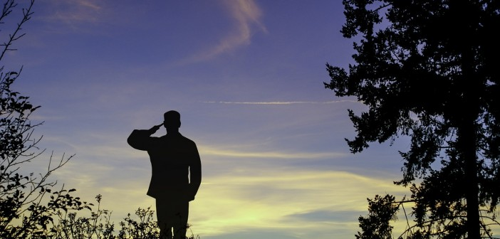 Stock photo of a heavily back-lit soldier saluting outdoors