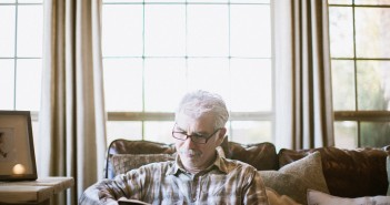 Stock photo of an older white man sitting on a sofa and reading in his living room
