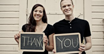 "Stock photo of a young white man and woman holding up two chalkboards that read ""THANK YOU"""